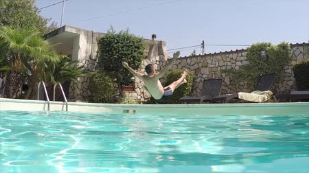 Slow motion of a Caucasian man back jumping in the swimming pool.