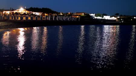 Lights reflected in the water of the sea at night, on a beach, with small waves scattered on the sand, in Marina Di San Nicola, Lazio, Italy. Stock Footage