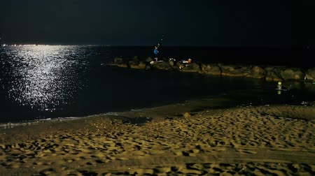 Boys fishing on a beach by night in the light of the full moon. Unrecognizable people.