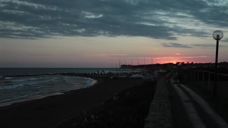 A Mediterranean beach in the evening with the sun disappearing on the horizon, Marina Di San Nicola, Lazio, Italy.