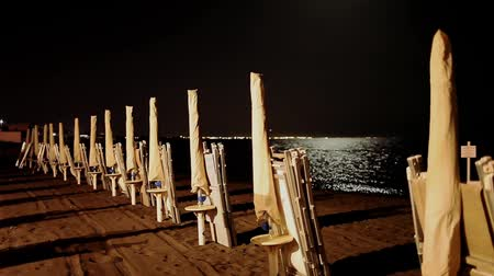 Closed umbrellas arranged in a raw on a beach by night with full moon.