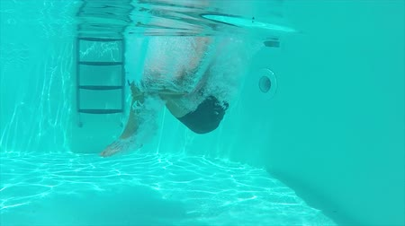 Underwater view of man jumping inside the pool, slow motion.