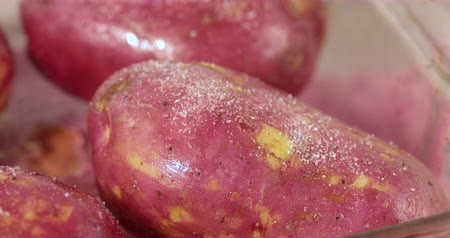Seasoning raw red potatoes for baking with salt and pepper.
