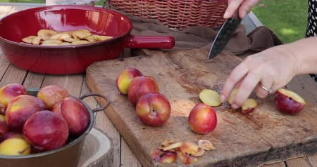 Woman cooking outdoor a cake cutting plums thinly sliced on an old used wooden cutting board and adding them in a terracotta baking pan