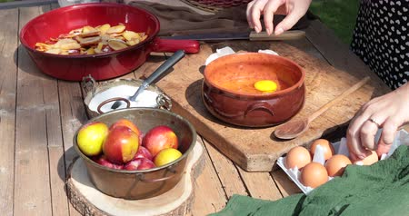 Woman out in the garden preparing a cream to make the plum tart mixes eggs with sugar in a bowl