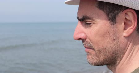 Close-up view of the face of an unshaven Caucasian man wearing a white hat looking at the sea while relaxing trying to regain his balance.