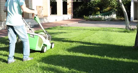 Man cutting the lawn in front of the house with the lawn mower -