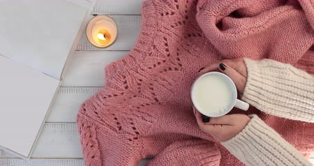 A woman warms hands on a mug of hot milk - A woman relaxes with a cup of hot milk in a cozy ambient with a book candle light and warming up her hands in woollen sweaters.