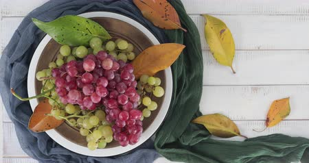 Plate with pink and white table grapes decorated with autumn leaves rotating on a white wooden table - Table top view with copy space Stock Footage