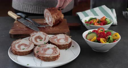 ロイン : Roasted pork loin stuffed with ground sausage cut in slices and decorated with fresh myrtle leaves - Woman in the kitchen preparing roasted meat roll and salad for dinner 動画素材