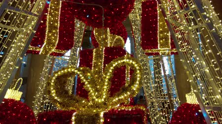 Huge Christmas tree of  lights and golden garlands, with big red balls and presents Stock Footage