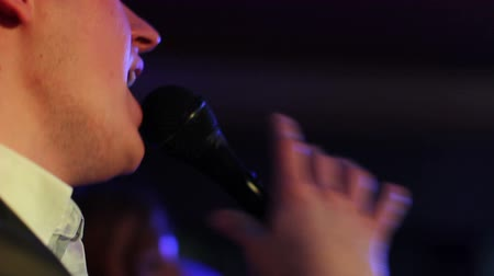 cantora : singer singing into a microphone with bokeh effect, close up