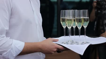 porce : Waiter offer a glass of champagne on a tray. can be used for stories about restaurants, parties, weddings, birthdays Dostupné videozáznamy