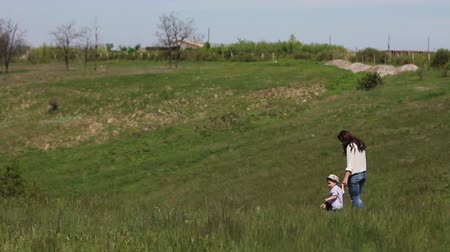 took : mom and son walking on grass at summer day Stock Footage