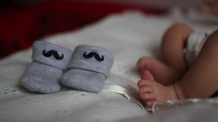 nascido : newborn feet near booties Stock Footage