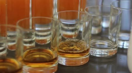 nightcap : Hand of the waiter pours whiskey to glasses Stock Footage