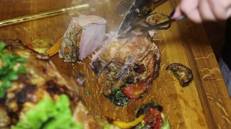 spaniard : waiter cuts the finished steaming meat on a wooden board