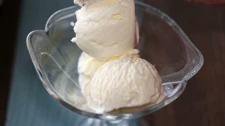 vanilya : Putting scooped vanilla ice cream ball to glass bowl Stok Video