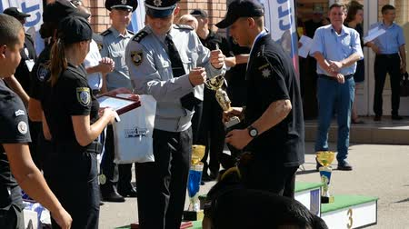 fiel : DNIPRO, UKRAINE- AUGUST 7, 2018: policeman give winners cup to cop and put on gold medal to him and k9 german shepherd dog on August 7, 2018 in Dnipro, Ukraine