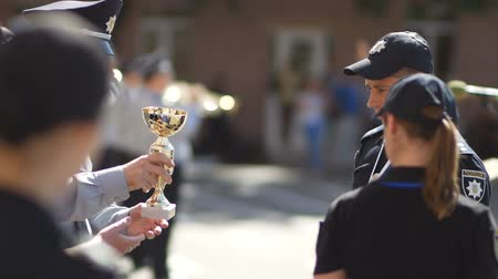 first officer : DNIPRO, UKRAINE- AUGUST 7, 2018: policeman give winners cup to cop and put on gold medal to him and k9 german shepherd dog on August 7, 2018 in Dnipro, Ukraine