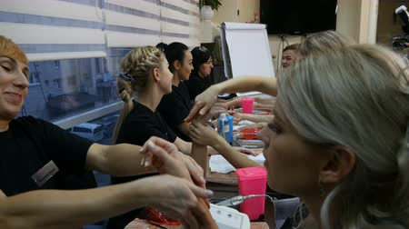 teszi : DNIPRO, UKRAINE- DECEMBER 14, 2017: women in pairs do massage of the hands at the cosmetology training on December 14, 2017 in Dnipro, Ukraine Stock mozgókép