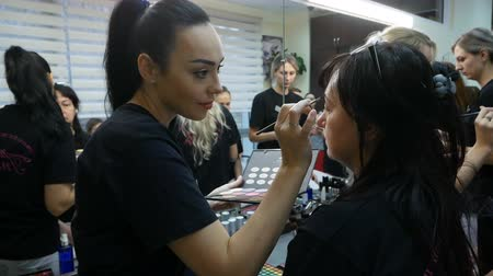 instruções : DNIPRO, UKRAINE- DECEMBER 14, 2017: students training to become makeup artist at beauty studio on December 14, 2017 in Dnipro, Ukraine