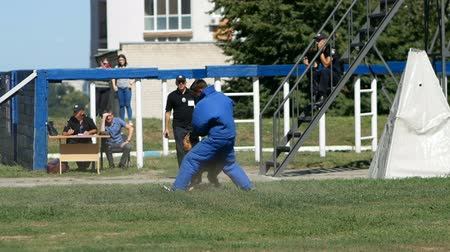 felon : DNIPRO, UKRAINE- AUGUST 7, 2018: Military training. Army dog attacking a suspect man wearing protective cloth at national championship of canine national polices on August 7, 2018 in Dnipro, Ukraine
