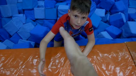 assentado : DNIPRO, UKRAINE-April 27, 2018: Children funny games in foam rubber pit in trampoline center, April 27, 2018 in Dnipro, Ukraine