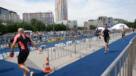 yarışçı : DNIPRO, UKRAINE-June 9, 2019: Dnipro Triathlon Festival, athletes running to cycling competitions, June 9, 2019 in Dnipro, Ukraine Stok Video