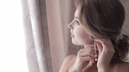 brincos : The young beautiful woman puts on earrings Stock Footage