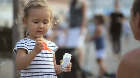 bright bubble : Cute little girl is blowing soap bubbles in the park.