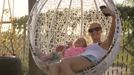 make photo : Young mom and cute daughter take selfie photo via smart phone swaying on swing