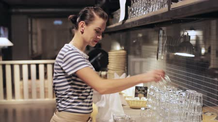 wipe away : Female waiter wiping a glass at cafe
