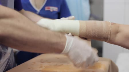 uložit : Doctor lay on gypsum on the hand female patient