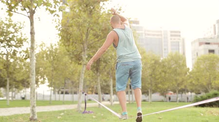 tightrope : Guy walks on slackline at public park