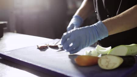 yemek tarifi : Hands of chef cutting fresh raw meat on a kitchen board in commercial kitchen