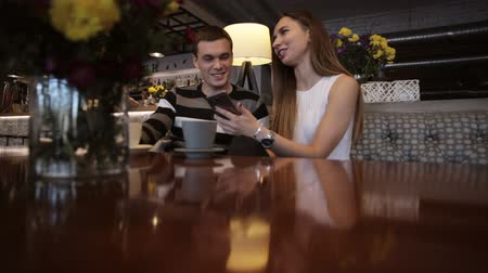 coffee time : Two young caucasian people watching a smartphone in a cafe and laughing