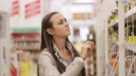 selecionar : Young woman is choosing seasoning in the shopping centre. Vídeos