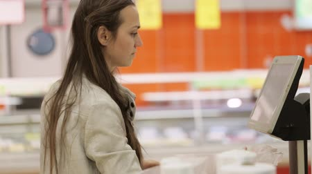 баланс : Young woman weighing the goods with electric scales in the supermarket.