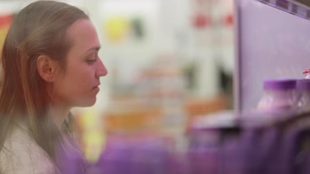açougue : Woman choosing refrigerated groceries at supermarket. Through the glass shot.