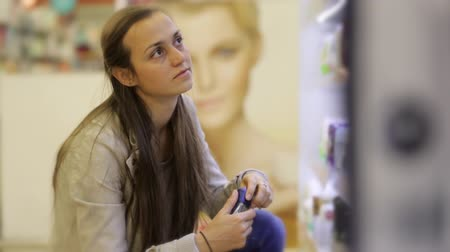 antiperspirant : Young caucasian woman choosing deodorant in beauty section of shoping centre.