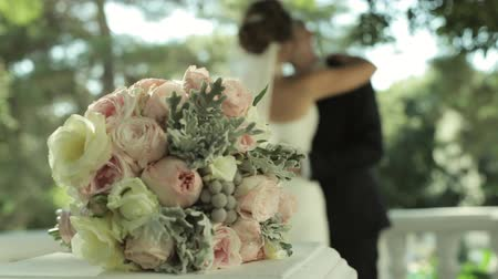 núpcias : Brides bouquet and kissing married couple on the background. Vídeos