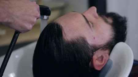 anelzinho : Man barber washing male client hair in a barbershop, close-up Stock Footage