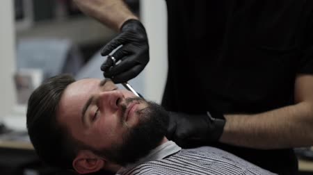 борода : Male barber cutting beard with scissors at a barber shop. Стоковые видеозаписи