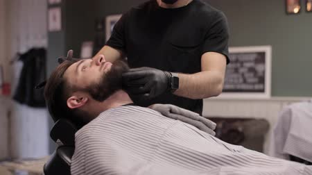 shaves : Barber putting a towel on chest of client and starts a dangerous shaves. Stock Footage