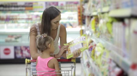 kordé : Mother and little daughter selecting a flakes at the supermarket Stock mozgókép
