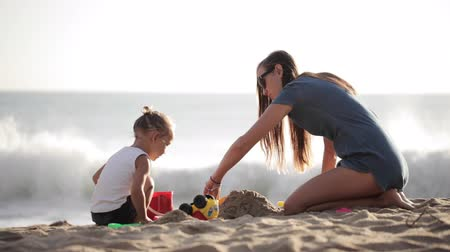 zabawka : Young mother with little doughter playing with sand on the beach