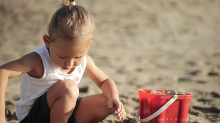 toy : Baby girl playing with red toy bucket and shovel on the sandy beach