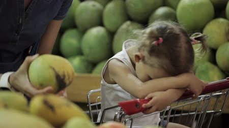 oneself : Baby get tired sit in shopping cart when her mom selecting fruits in supermarket