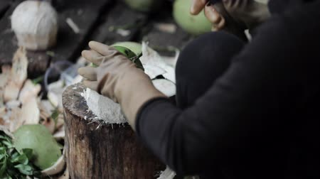 glove : Street seller opening coconut with a big knife.